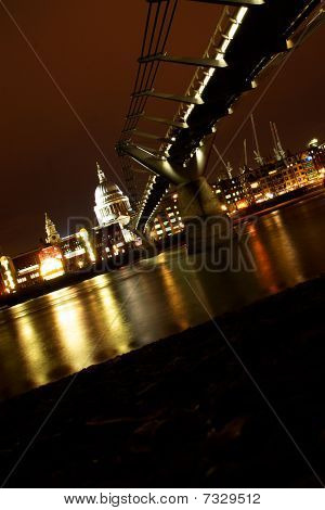 Night view of St. Paul Cathedral and the London skyline seen across the Thames from the river bank under the Millennium bridge, in front of the Tate Modern art gallery.