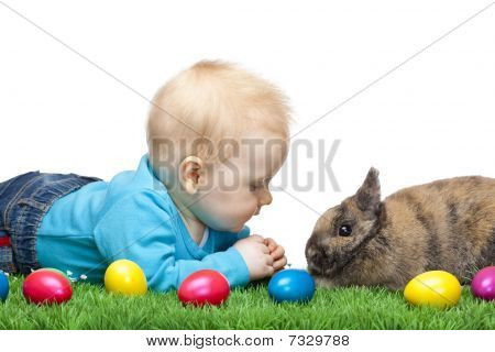 Male Young Baby Sitting In Meadow Together With Easter Bunny And Colorful Eggs.
