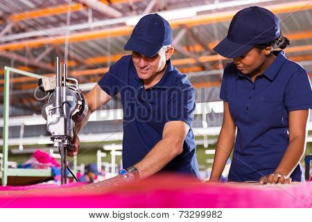 senior textile worker teaching new employee about cutting material