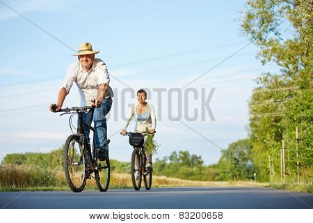 Senior couple riding bikes through summer landscape on a road