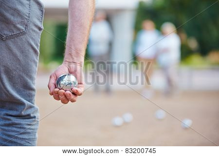 Hand holding a metal ball for playing boule