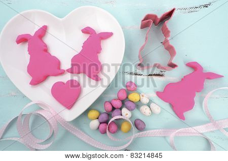 Happy Easter Pink Confectionary Sugar Fondant Cookie Bunnies On White Heart Shape Plates On Pale Aqu