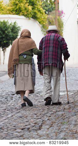 Old couple walking side by side