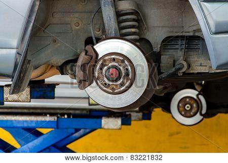 Car Under Repair On Hoist At Service Station