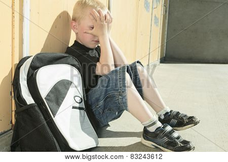 A very sad boy in school playground