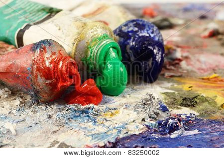 Art still life - closeup of three oil paint tubes with redgreen and blue colours background for creative art design poster