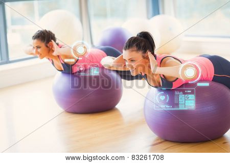 Two fit women exercising on fitness balls in gym against fitness interface