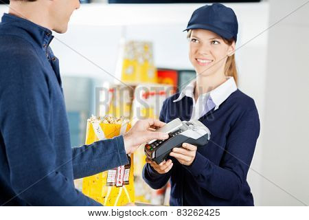 Happy female worker accepting payment through NFC technology from man at concession counter in cinema
