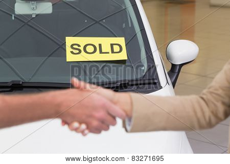 Person shaking hands in front of a sold car at new car showroom