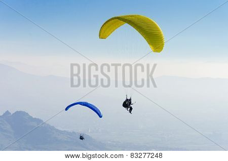 Paragliders in the Alps against blue clear sky