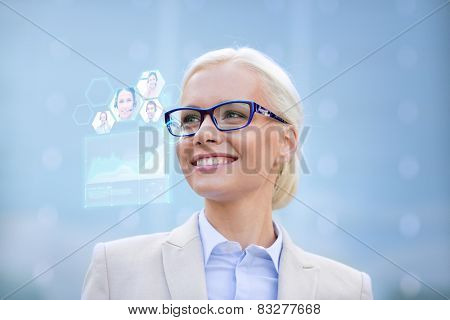 business, people, future technology and communication concept - young smiling businesswoman in eyeglasses with virtual screen, video chat and charts projection outdoors