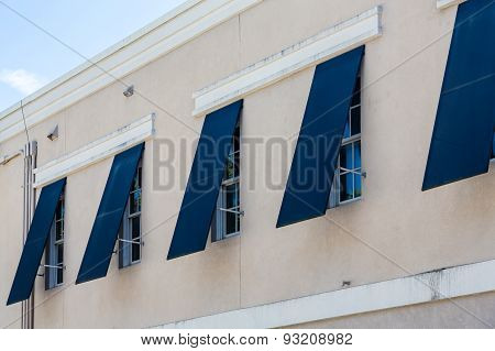 Blue storm shutters open on a new stucco building poster
