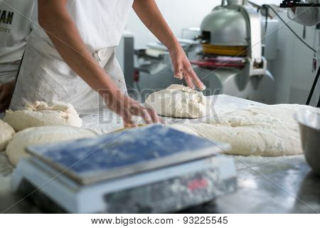 Baker Tossing Flour On Raw Dough