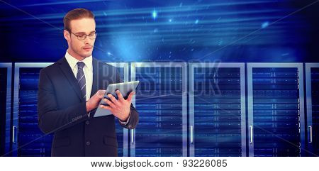 Unsmiling businessman using tablet pc against composite image of server towers