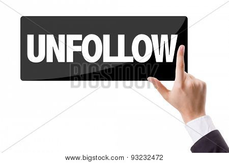 Businessman pressing button with the text: Unfollow