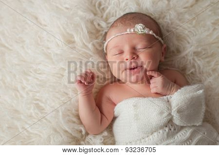 Newborn Baby Girl Wearing A White Knitted Bonnet