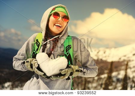 Winter sport, snowboarding - portrait of young snowboarder girl With snow heart in hands