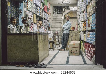JODHPUR, INDIA - 16 FEBRUARY 2015: Three Indian men in textile store. Post-processed with grain and texture.