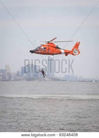 STATEN ISLAND, NY - MAY 24 2015: A Coast Guard rescue swimmer waves when hoisted by line into a US Coast Guard MH-65 Dolphin helicopter for a Search and Rescue demonstration for Fleet Week 2015.