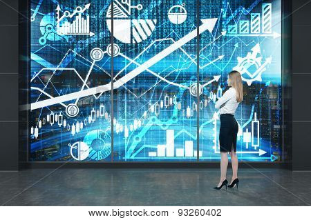 Full Length Of Young Lady Who Is Standing In Front Of The Digital Screen With Graphs, Charts And Arr