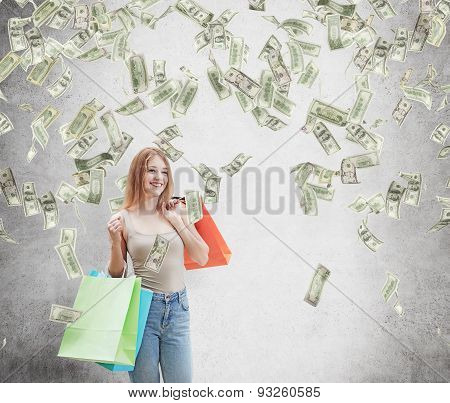 A Happy Young Woman With The Colourful Shopping Bags From The Fancy Shops. Dollar Notes Are Falling