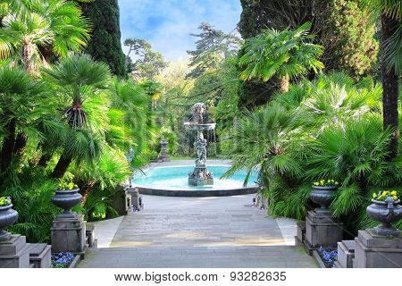 Walkway In A Beautiful Park With Palms, Thuyas And Fountain
