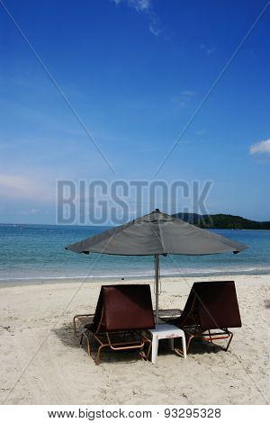 Couple of chairs on tropical sandy beach