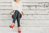 Lady with red high heel shoes sitting on stairs poster