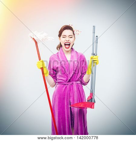 Tired pretty young housewife with mop, cleaning brush and dustpan standing and shouting