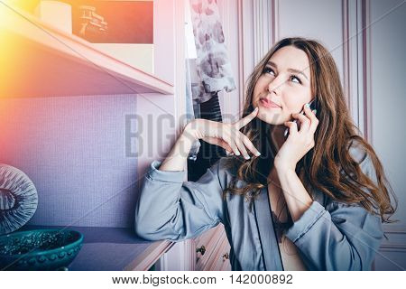 Young smiling beautiful woman choosing what to wear and using mobile phone in a closet