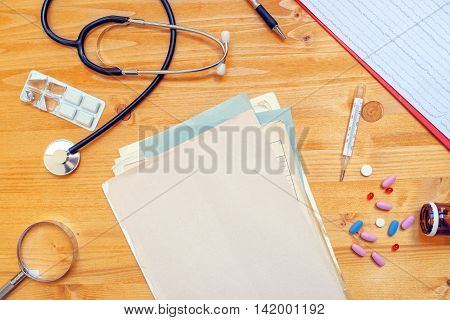 Assorted office supplies on general medical practitioner work desk. Doctor's workspace as copy space top view.
