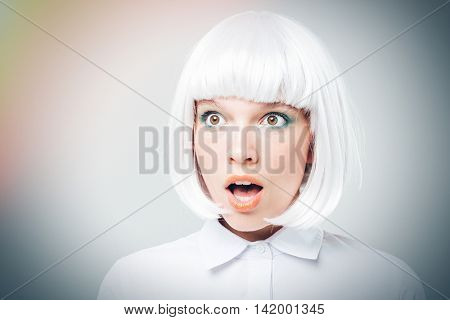 Closeup of amazed pretty young woman with mouth opened over white background