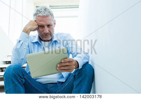 Tensed mature man holding tablet while sitting on steps at home