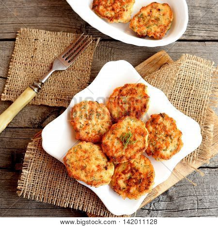 Fried fish cakes on a plate and on old wooden background. Cutlets cooked from salmon meat. Delicious and nutritious lunch or dinner recipe