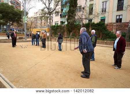 Barcelona Spain - April 4 2016: Petanque players in the park of Barcelona. Petanque is a game where the goal is to toss hollow steel balls as close as possible to a small wooden ball. Spain