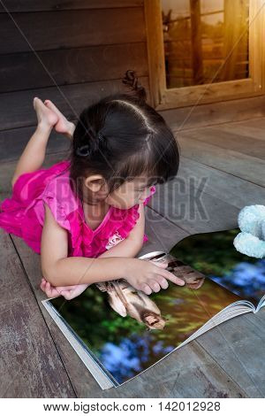 Closeup handsome asian girl smiling and reading picture album lying on wooden floor with bright sunlight outdoor at home. Children read and study education concept.