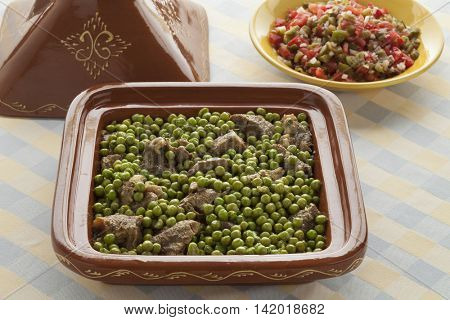 Traditional Moroccan dish with meat and green peas in a square tajine