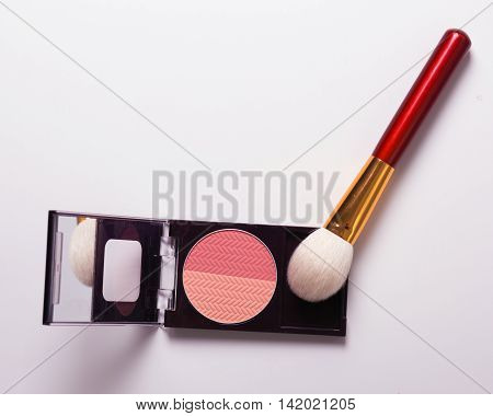 Golden cosmetics - powder blusher brush on light wooden background with copy space. flat lay.