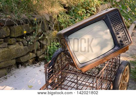 Retro Design TV on a Meadow with Iron Cart