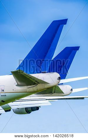 Two blue airliner tail planes parked side by side against a blue sky