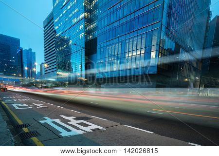 blurred traffic in downtown district,hong kong,china.Chinese characters on road are all traffic roadmarking.