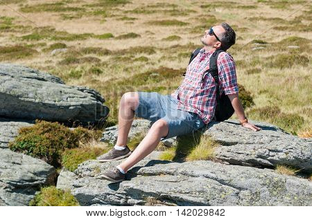 Male Backpacker Sun Bathing On Top Of The Mountain