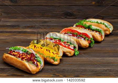 A lot of big delicious hot dogs with sauce and vegetables on wooden background. Their assorted hot dogs to gourmet.