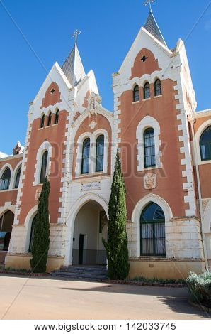 NEW NORCIA,WA,AUSTRALIA-JULY 15,2016: Red brick exterior of St. Gertrude's Ladies College with spanish gothic architecture and arched accents under a blue sky in the monastic town of New Norcia, Western Australia.