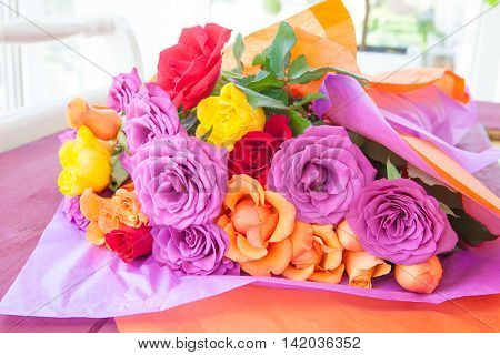 Fresh roses in bright colors wrapped in colorful paper