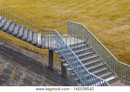 Old stairs and field with yellow grass.