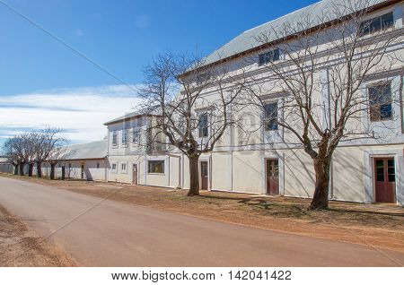 NEW NORCIA,WA,AUSTRALIA-JULY 15,2016: The Benedictine Monastery cream and white exterior with leafless trees in the historic monastic town of New Norcia, Western Australia.