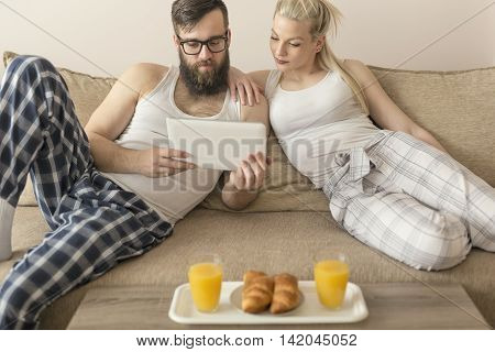 Couple in love sitting on the couch in the living room wearing pajamas after getting up in the morning reading news on a tablet computer and having breakfast