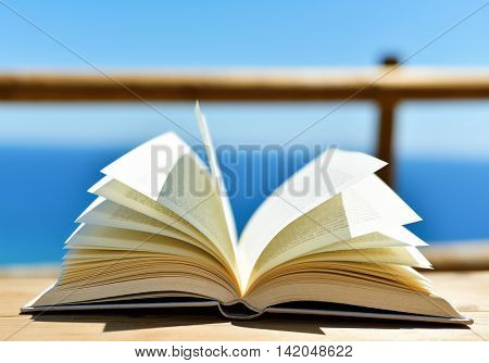 closeup of an open book on a wooden table outdoors, with the ocean in the background