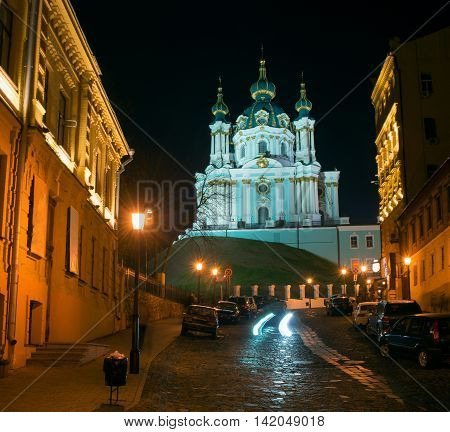 Andriyivskyy Descent with the Saint Andrew's Church (Kiev) night view. All buildings are illuminated.